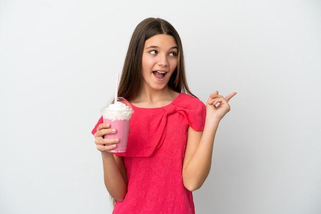 Menina com milk-shake de morango sobre fundo branco isolado com a intenção de descobrir a solução enquanto levanta um dedo