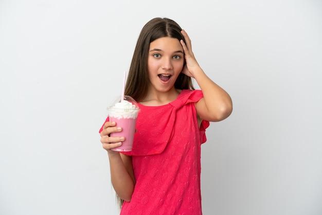 Menina com milk-shake de morango sobre fundo branco isolado com expressão de surpresa