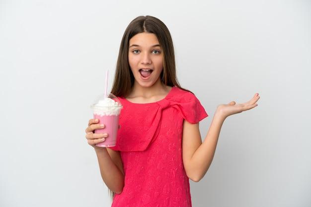 Menina com milk-shake de morango sobre fundo branco isolado com expressão facial de choque