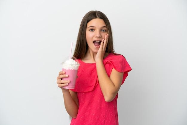 Menina com milk-shake de morango sobre fundo branco isolado com expressão facial surpresa e chocada