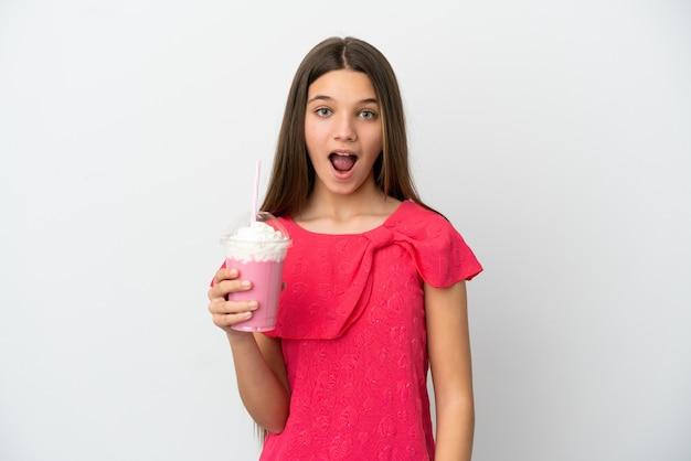 Menina com milk-shake de morango sobre fundo branco isolado com expressão facial surpresa