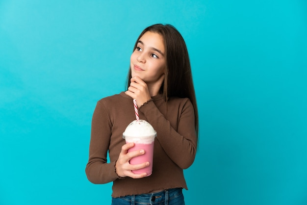 Menina com milkshake de morango isolada em um fundo azul e olhando para cima