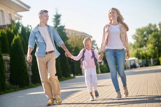 Menina com mochila caminhando com os pais