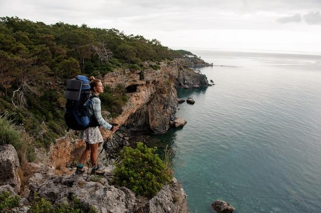 Menina com mochila de pé sobre a rocha com bengalas