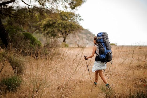 Menina com mochila e bengalas andando pelo campo