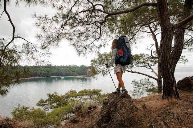 Menina com mochila e bengalas de pé na colina rochosa debaixo da árvore