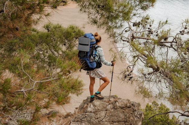 Menina com mochila e bengalas em pé sobre a rocha entre galhos de árvores