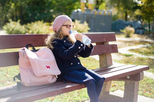 Menina com mochila escolar, bebendo água