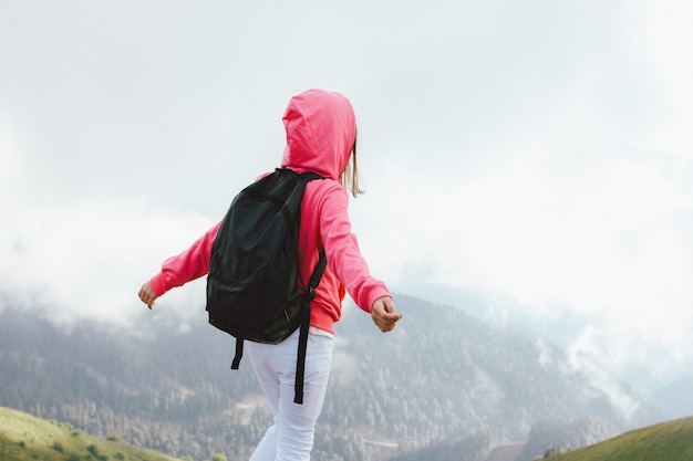 Menina com mochila nas belas montanhas nubladas