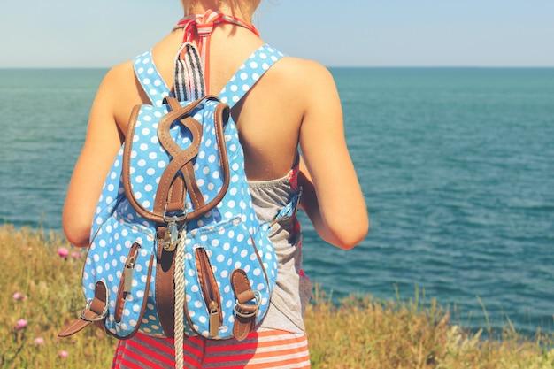 Menina com mochila, olhando para o mar