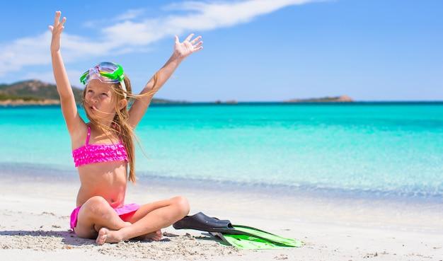 Menina com nadadeiras e óculos de proteção para ssnorkling na praia