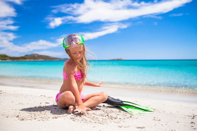 Menina com nadadeiras e óculos para snorkling