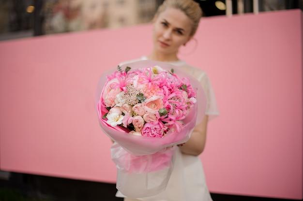 Menina com o buquê de flores cor de rosa