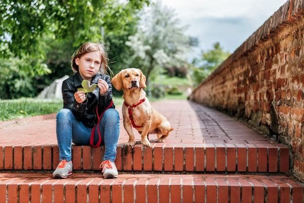 Menina com o cachorro desfrutando ao ar livre