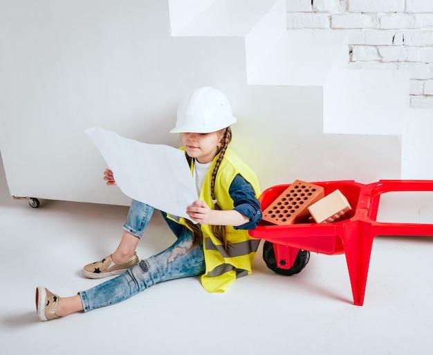 Menina com o carrinho de mão no fundo branco. construção