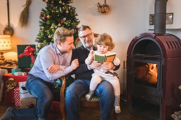 Menina com o pai e o avô lendo um livro no natal
