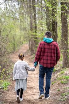 Menina com o pai no parque no início da primavera em clima frio, vista de trás.