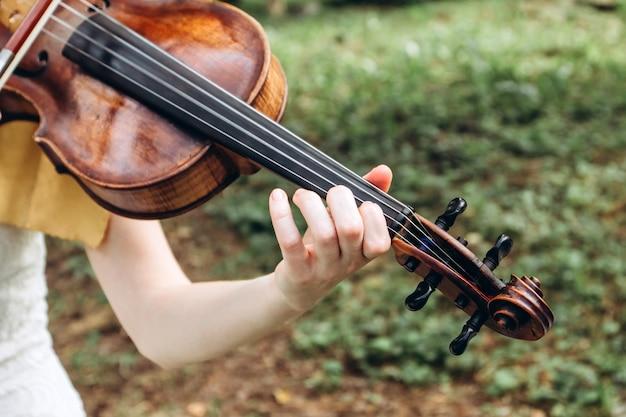 Menina com o pescoço do violino closeup.
