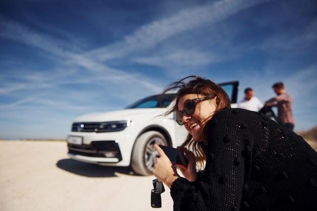 Menina com o telefone nas mãos sorrindo e se senta contra um carro branco e pessoas ao fundo.