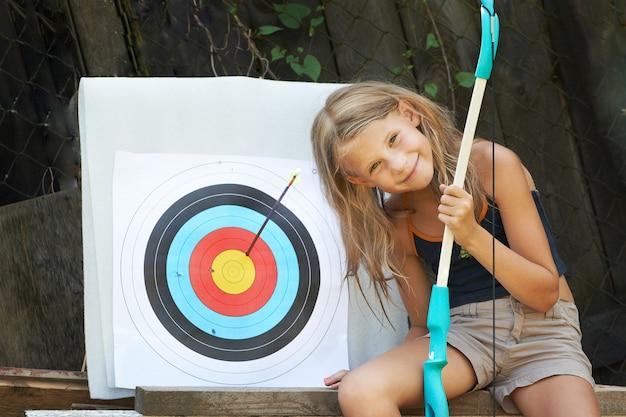 Menina com objetivo de arco e esportes