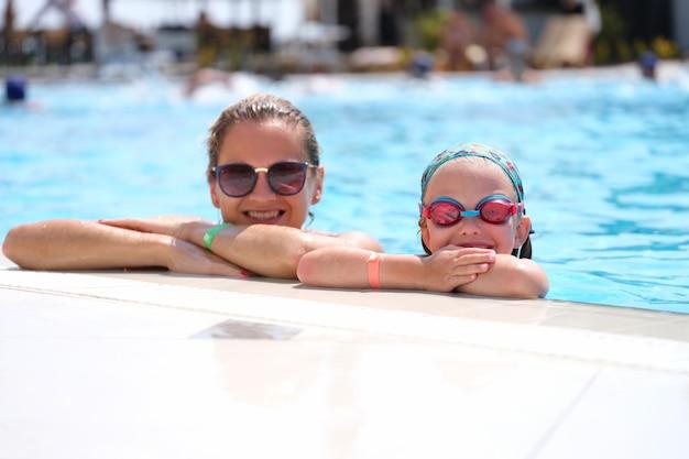 Menina com óculos de natação e mãe deitada na beira da piscina