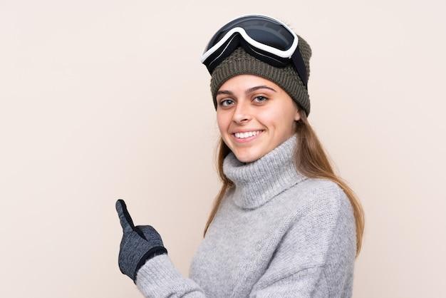 Menina com óculos de neve sobre parede isolada