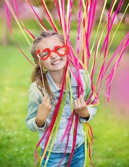 Menina com óculos de papel engraçado