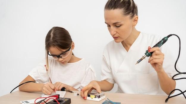 Menina com óculos de proteção e professora fazendo experiências científicas