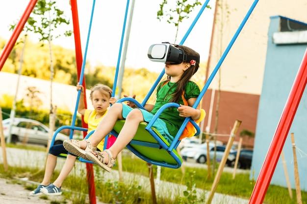 Menina com óculos de realidade virtual em um playground