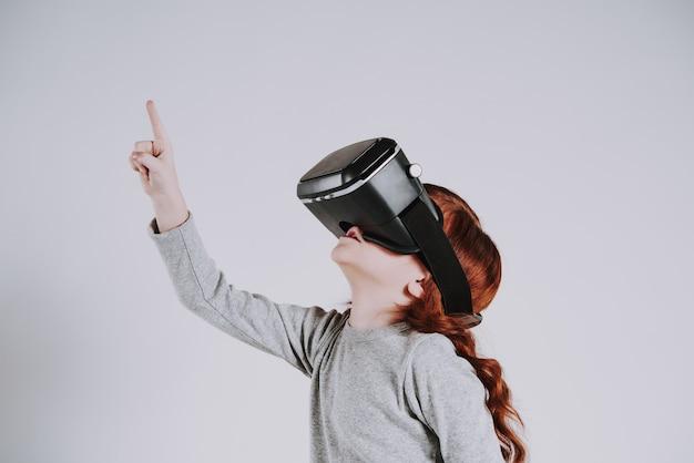 Menina com óculos de realidade virtual joga o jogo