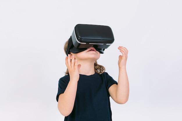Menina com óculos de realidade virtual olhando para um fundo branco