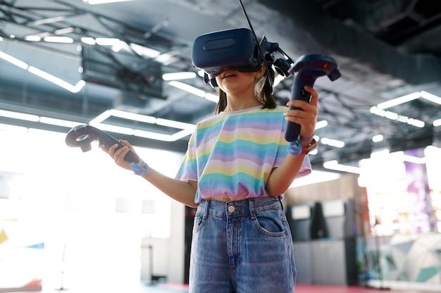 Menina com óculos de realidade virtual tem joysticks nas mãos. criança jogando videogame 3d no centro de entretenimento. crianças se divertindo, criança passando o fim de semana no parquinho, infância feliz