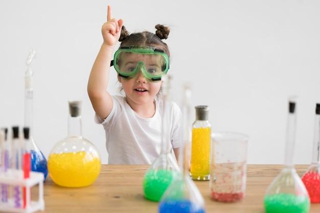 Menina com óculos de segurança em laboratório