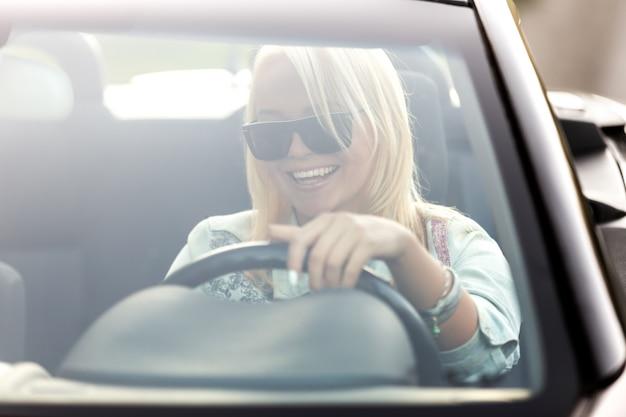 Menina com óculos de sol condução