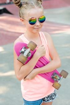 Menina com óculos de sol e skate cor de rosa