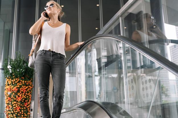Menina com óculos de sol, falando em seu telefone móvel em uma escada rolante