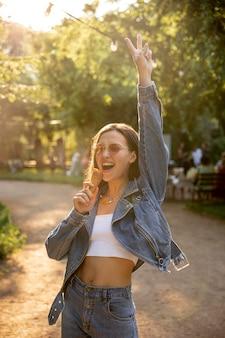 Menina com óculos de sol no parque tomando sorvete