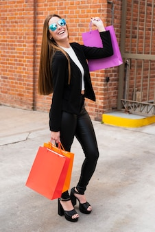 Menina com óculos de sol segurando sacolas de compras