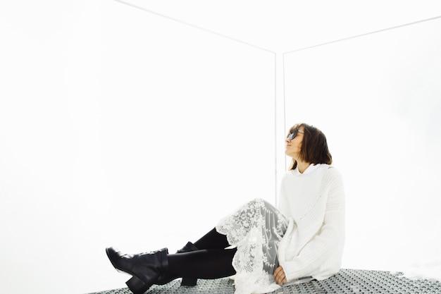 Menina com óculos de sol senta-se no chão
