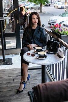 Menina com óculos de sol, sentada em um café, cafeteria, sentada em uma cadeira na cidade com flores vermelhas, usando óculos de sol