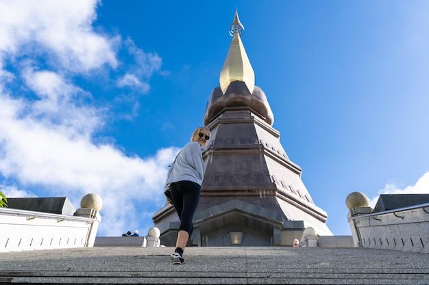 Menina com óculos de sol subindo os degraus de um pagode