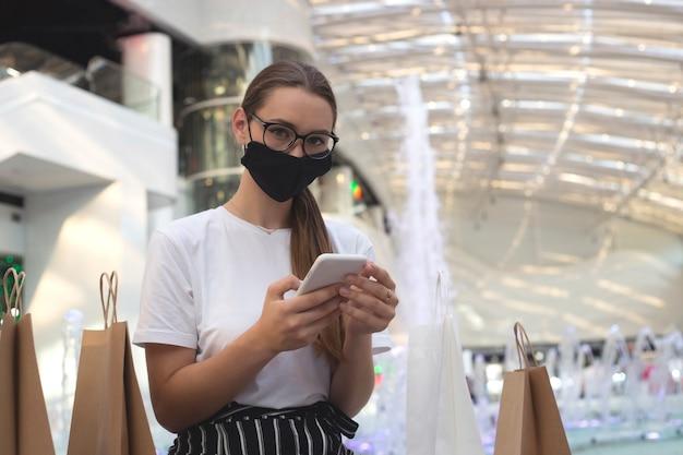 Menina com óculos e máscara protetora em um shopping com compras