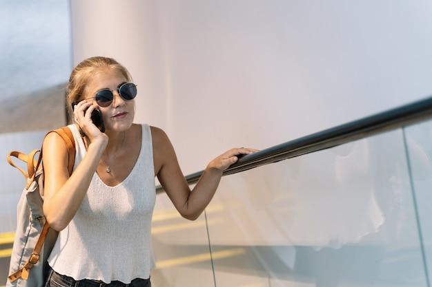 Menina com óculos escuros e uma bolsa pendurada no ombro dela falando em seu telefone móvel em uma escada rolante