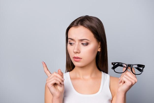 Menina com óculos na mão isolada em cinza