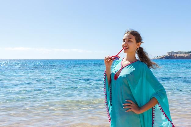 Menina com óculos na praia em dia ensolarado