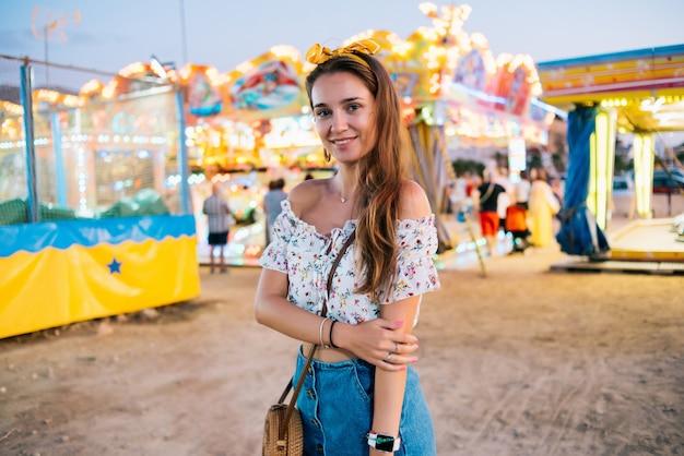 Menina com óculos redondos, cabelo castanho, saia jeans e uma bolsa redonda no fundo de um parque de diversões
