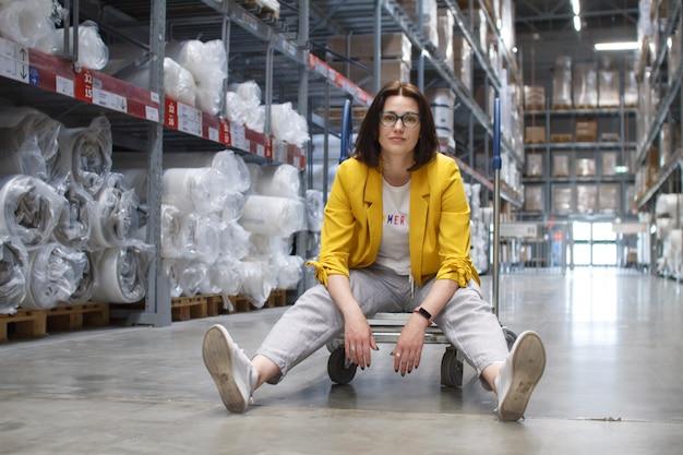 Menina com óculos sentado em um carrinho de compras em uma loja no armazém