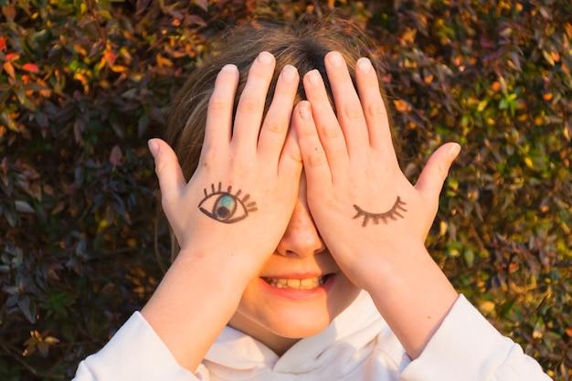 Menina, com, olho, tatuagens, ligado, mão palma, cobertura, dela, olhos