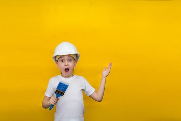 Menina com olhos bem abertos e boca em um capacete de construção segura um pincel