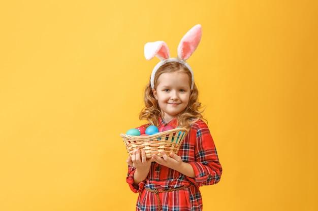 Menina com orelhas de coelho com uma cesta de ovos de páscoa.